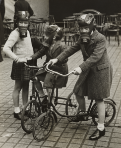 Children playing on bicycles wearing their gas masks, ca. 1940s