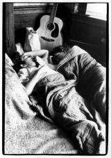 Couple lying on a floor; guitar resting above them