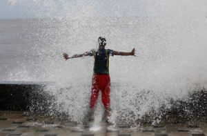 A boy gets drenched in a large wave during high tide at a sea front in Mumbai, India, June 15, 2015. REUTERS/Danish Siddiqui