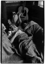 Hippie couple in bed with guitar in background
