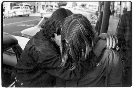Man and woman embracing on sidewalk near car