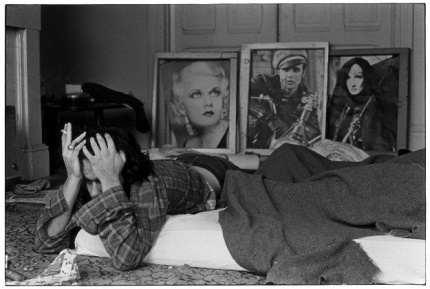 Man holding head with both hands and smoking a cigarette while lying on a mattress on the floor. Posters of movie stars on the wall behind - James Dean, et. al