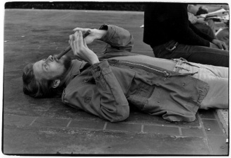 Man lying on pavement playing a wooden flute