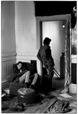 Man sleeping in chair while another stands in doorway