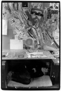Man sleeping under a makeshift table with a collage on the wall behind
