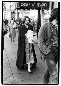 Man walking down sidewalk wearing long dress and a long cloak, carrying a cotton mop head