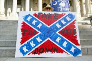 Jay Bender holds a sign asking for the removal of the confederate battle flag that flies at the South Carolina State House in Columbia, SC June 20, 2015.  REUTERS/Jason Miczek - RTX1HF36