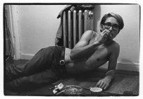 Shirtless young man lying on the floor smoking