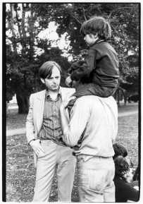 Tom Wolfe listening to a man with a small boy on his shoulders in the Panhandle