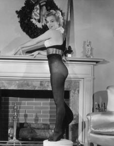 American actor Marilyn Monroe (1926 - 1962) poses while standing inside an oversized nylon Christmas stocking beside a fireplace, 1951. Monroe wears a two-piece bathing suit. (Photo by Hulton Archive/Getty Images)