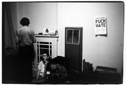 Two people in a room with a poster reading %22Fuck Hate%22