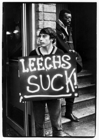 Young man holding a sign reading %22Leechs suck!%22