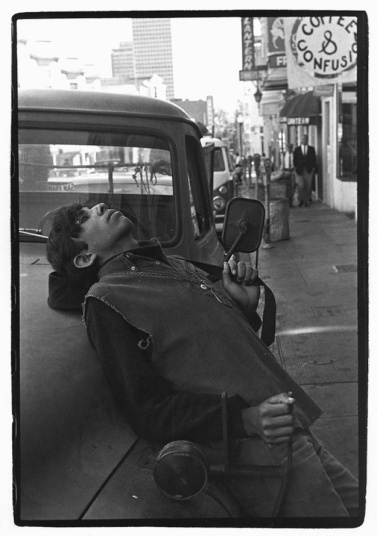 Young man leaning over onto the hood of a truck on Broadway