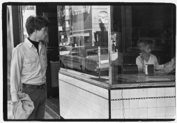 Young man looking into window of a diner on Broadway where a woman smokes and reads a newspaper