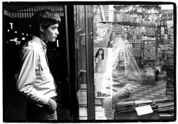 Young man looking through window of adult newsstand