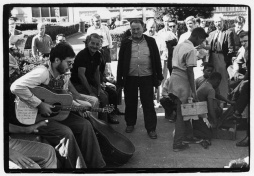 Young man playing guitar in protest of the Vietnam war, older hecklers and crowd looking on; African-American boys giving shoe shines
