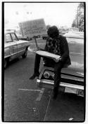 Young man sitting on a car near Ashbury, holding sign advertising free movies, and reading a newspaper