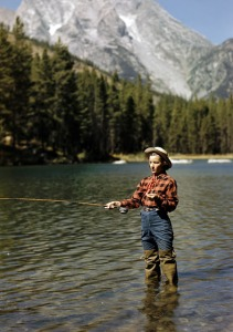 Young cowgirl Esther Allen trout fishing in String Lake. Teton Mountains behind.