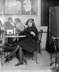 A fashionable young woman pours alcohol into a cup from a cane, February 1922