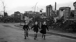 Three girls skate home from school, past blocks of houses destroyed by Allied air raids, Essen, Germany, February 14, 1949