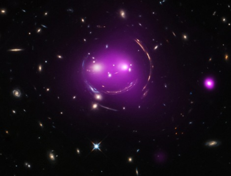 "Astronomers think that in the future the ""Cheshire Cat"" group will become what is known as a fossil group, a gathering of galaxies that contains one giant elliptical galaxy and other much smaller, fainter ones. Today, researchers know each ""eye"" galaxy is the brightest member of its own group of galaxies and these two groups are racing toward one another at over 300,000 miles per hour. Data from Chandra (purple), which has been combined with optical data from Hubble, show hot gas that has been heated to millions of degrees, which is evidence that the galaxy groups are slamming into one another. Chandra's X-ray data also reveal that the left ""eye"" of the Cheshire Cat group contains an actively feeding supermassive black hole at the center of the galaxy."