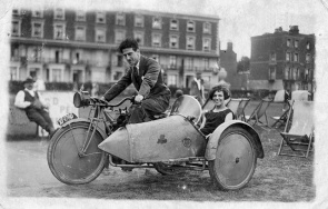 A couple on a motorcycle at the beach in Margate, England, ca. 1920s