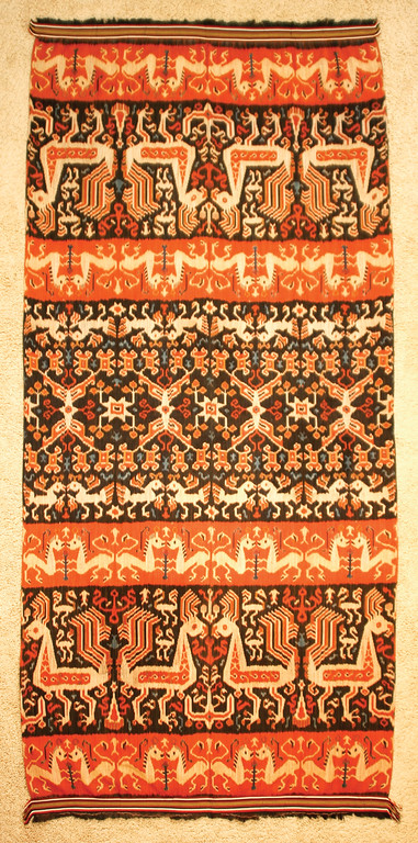 Dancing Threads Dancing Threads TAPIS Origin: Lampung, South Sumatra, Indonesia These intricate, elaborate skirts are hand dyed and hand woven by women to wear during important ceremonies. First woven and sewn into a large rectangle, the sides were then joined to create a tube for the woman to step into and wear as a sarong. Due to Lampung's position along major maritime routes and their own production of desirable trade goods, such as pepper and gold, the women of Lampung had ready access to a variety of iconography from other cultures and a wide range of trade materials. This wealth is on display here with the imaginative use of silk, cotton, mica and gold. The skills necessary to create these tapis gradually diminished during the early part of the twentieth century and were extinguished completely during World War II. Dancing Threads Dancing Threads HINGGI SUMBA ISLAND, INDONESIA Large, bold designs characterize the hinggi (men's blankets) from the island of Sumba. The ikat patterns are dyed and woven by hand. Hinggi are usually made in pairs but then separated for reasons of utility, ritual or ceremony. Such pieces would be worn by a Sumbanese man - one around his hips, the other one around his shoulders. The finest hinggi were made as gifts to the nobility in order to be buried with them, with the unfortunate consequence that many of the most beautiful are gone.