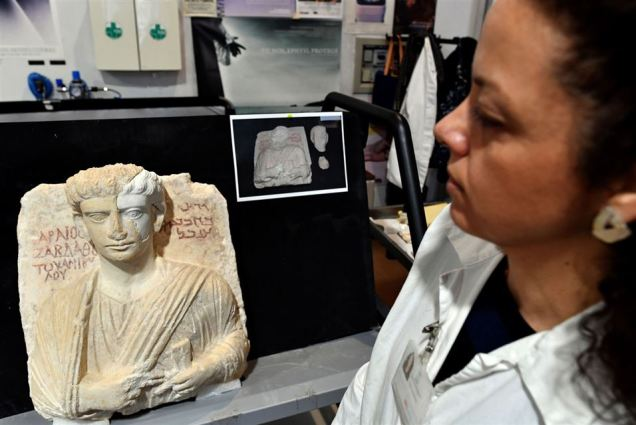 A restorer looks at a bust, which is one of the two funeral reliefs from Palmyra archeological site that will be restored at the Higher Institute of Conservation and Restoration (ISCR - Istituto Superiore per la Conservazione ed il Restauro) in Rome, on February 16, 2017. The busts of a man and a woman, dated from the 2nd and 3rd century AD and destroyed by the Islamic State group (IS), have been entrusted to the care of the technical and restorers of the ISCR in Rome. By the end of this month, they will be returned to their place of origin. Alberto PIZZOLI / AFP