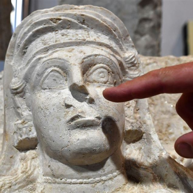 A restorer points the missing nose of a woman bust, which is one of the two funeral reliefs from Palmyra archeological site that will be restored at the Higher Institute of Conservation and Restoration (ISCR - Istituto Superiore per la Conservazione ed il Restauro) in Rome, on February 16, 2017. The busts of a man and a woman, dated from the 2nd and 3rd century AD and destroyed by the Islamic State group (IS), have been entrusted to the care of the technical and restorers of the ISCR in Rome. By the end of this month, they will be returned to their place of origin. Alberto PIZZOLI / AFP