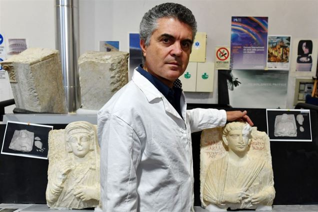 Italian Restorer Antonio Iaccarino poses in front of the two funeral reliefs from Palmyra archeological site that will be restored at the Higher Institute of Conservation and Restoration (ISCR - Istituto Superiore per la Conservazione ed il Restauro) in Rome, on February 16, 2017. The busts of a man and a woman, dated from the 2nd and 3rd century AD and destroyed by the Islamic State group (IS), have been entrusted to the care of the technical and restorers of the ISCR in Rome. By the end of this month, they will be returned to their place of origin. Alberto PIZZOLI / AFP