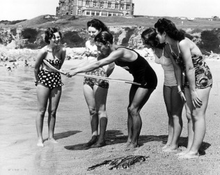 August 1950: A lifeguard teaches four young women how to handle a surfboard on the beach at Newquay in Cornwall. (Photo by J. R. T. Richardson/Fox Photos/Getty Images)
