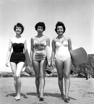 31st May 1955: Three surfing girls (left to right, Marilyn Ridge, Lyn Connelly, Dee Delaney) wax their surfboards and prepare to ride the swell and maybe catch a tube or two down on Newquay beach, Cornwall. (Photo by Russell Knight/BIPs/Getty Images)