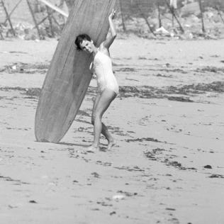 16 yr. old surfer Kathy (Gidget) Kohner on the beach with her surfboard.